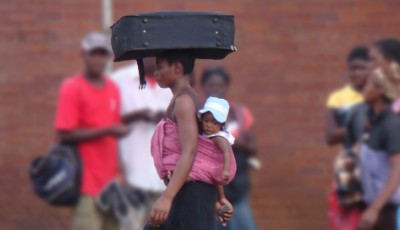 Woman with child on her back and suitcase on her head (Harare, Zimbabwe)