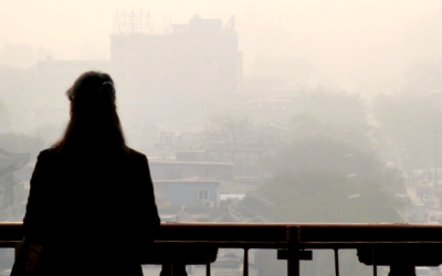 A solo traveler taking in the view overlooking the smog-covered Hutongs of Beijing.